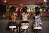 Hispanic women sitting at bar