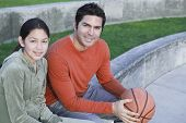 Hispanic father and daughter with basketball