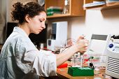 stock photo of electrophoresis  - Female researcher in a lab performs sample preparation for DNA electrophoresis making dots of ethidium bromide - JPG
