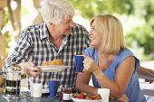 Senior couple eating breakfast outdoors