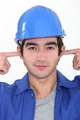 Tradesman plugging his ears
