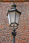 historic street lamp in front of red brick wall