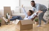 Excited African American Man Riding Woman In Cardboard Box Celebrating Moving Into New House. Select poster