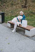 Smiling Elderly Woman Sitting With Pedigree Dog poster