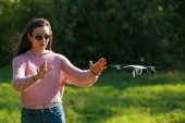 Walk With A Drone. A Young Woman In Black Glasses Launches A Low Flying Drone. Reaches Out To A Low  poster
