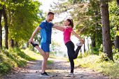 young happy couple enjoying in a healthy lifestyle warming up and stretching before jogging on a cou poster