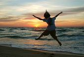 Cild Jumping For Joy At Sunrise On The Beach