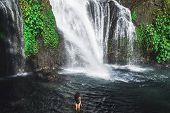 Young Slim Brunette Woman With Curly Hair Enjoying In Lagoon Of Huge Tropical Waterfall Banyumala In poster