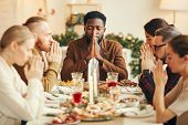 Portrait Of African-american Man Saying Grace Sitting At Dinner Table During Christmas Banquet With  poster