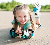 stock photo of cute little girl  - Little girl in roller skates at a park - JPG