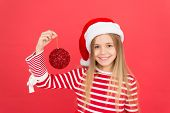 Decorate Christmas With Joy. Little Santa Girl Hold Christmas Tree Ball. Happy Child Smile With Red  poster