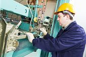 stock photo of adjustable-spanner  - One machinist worker at work adjusting elevator mechanism of lift with spanner - JPG