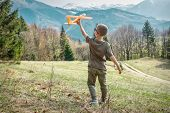 Young aviator boy with him airplane toy starting fly. Beautiful spreeng mountains view at sunny day. poster