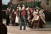 stock photo of antique wheelchair  - Tough cowboy with group of people in old west costumes - JPG