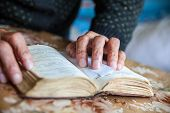 Old Woman Hands On The Open Prayer Book (christian Prayer Book In Ukrainian). Reading The Book. Pray poster