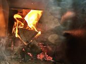 Fire In The Boiler, Closeup. Flames Of Fire In A Wood Burning Stove. Red Tongues Of Fire In A Rustic poster