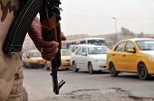 An Iraqi soldier armed with an assault rifle pointed to the ground watching traffic flow by at a roa