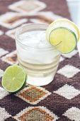 Wasser mit Zitrone und Limette In ein Glas mit Eis auf ethnische Matte