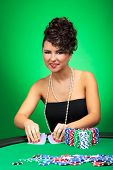 young sexy woman sitting at the poker table and shuffling cards while smiling at the camera, on a green background