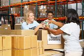 stock photo of warehouse  - Volunteers Collecting Food Donations In Warehouse - JPG