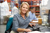 image of dispatch  - Businesswoman Working At Desk In Warehouse - JPG
