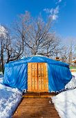 pic of yurt  - One blue yurt with big closed decorated orange door in the winter park - JPG