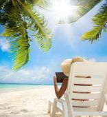 stock photo of palm-reading  - Tropical beach and woman relaxing with tablet computer sitting on the sun chair - JPG