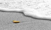 Yellow Rock On Sand In Front Of Water Wave