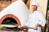 Chef puts dough in the oven for pizzas,