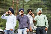 Group portrait of smiling authentic native indian punjabi sikh men in turban speaking on mobile phone