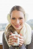Close-up portrait of a smiling young woman wearing earmuff with drinking coffee
