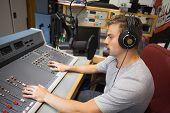 Handsome focused radio host moderating in studio at college