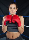 Portrait of a beautiful young woman in red boxing gloves in the ring