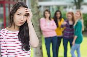 stock photo of peer-pressure  - Portrait of a female student being bullied by other group of students - JPG