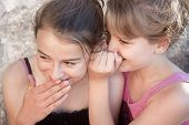 foto of bff  - Two pretty teenage girls gossiping giggling and whispering