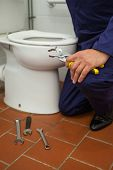 Close up of plumber holding pliers in public bathroom