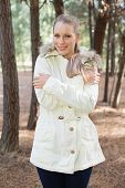 picture of shivering  - Cute woman shivering while having a walk in a forest on a winter day - JPG