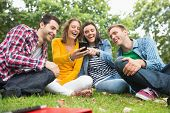 Group of happy young college students looking at mobile phone in the park