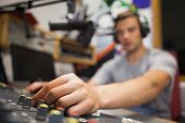 Handsome radio host moderating touching switch in studio at college