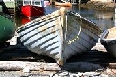 stock photo of dory  - wooden fishing dory pulled up on the shore - JPG