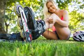 Casual happy blonde putting on roller blades in a park