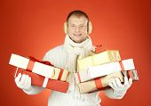 Portrait of happy man in white winterwear with stack of giftboxes looking at camera