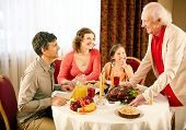 Portrait of happy family sitting at festive table and looking at senior man during Thanksgiving dinn