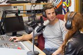 Attractive content radio host interviewing a guest in studio at college