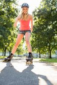 Casual smiling blonde inline skating on pathway in a park