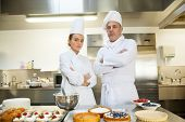 Serious chef and head chef standing arms crossed in professional kitchen