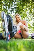 Casual smiling blonde tying shoelaces of roller blades in a park