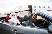 Portrait of Santa waving hand from convertible with private jet in background