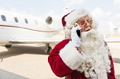 Surprised Santa Claus using mobile phone against private jet at airport terminal