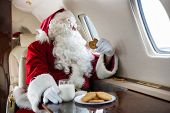 stock photo of jet  - Man in Santa costume holding cookie while looking through private jet - JPG
